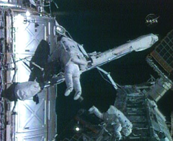 Spacewalkers Peggy Whitson and Dan Tani move a fluid tray outside the International Space Station during Saturday's spacewalk. Image credit: NASA TV