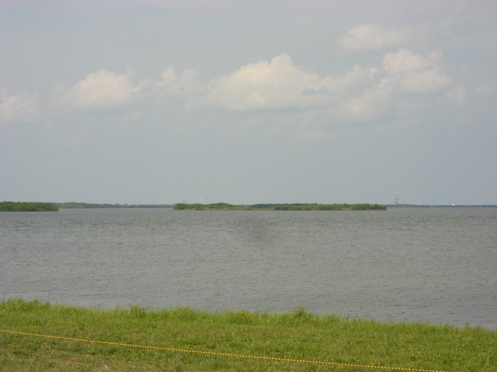 This is a view from the NASA Causeway of launch pad 39A (to the right, somewhat hard to see).Taken without zoom lens, it closely resembles what you see with your eyes. The Causeway viewing area is around six miles away from the pad.