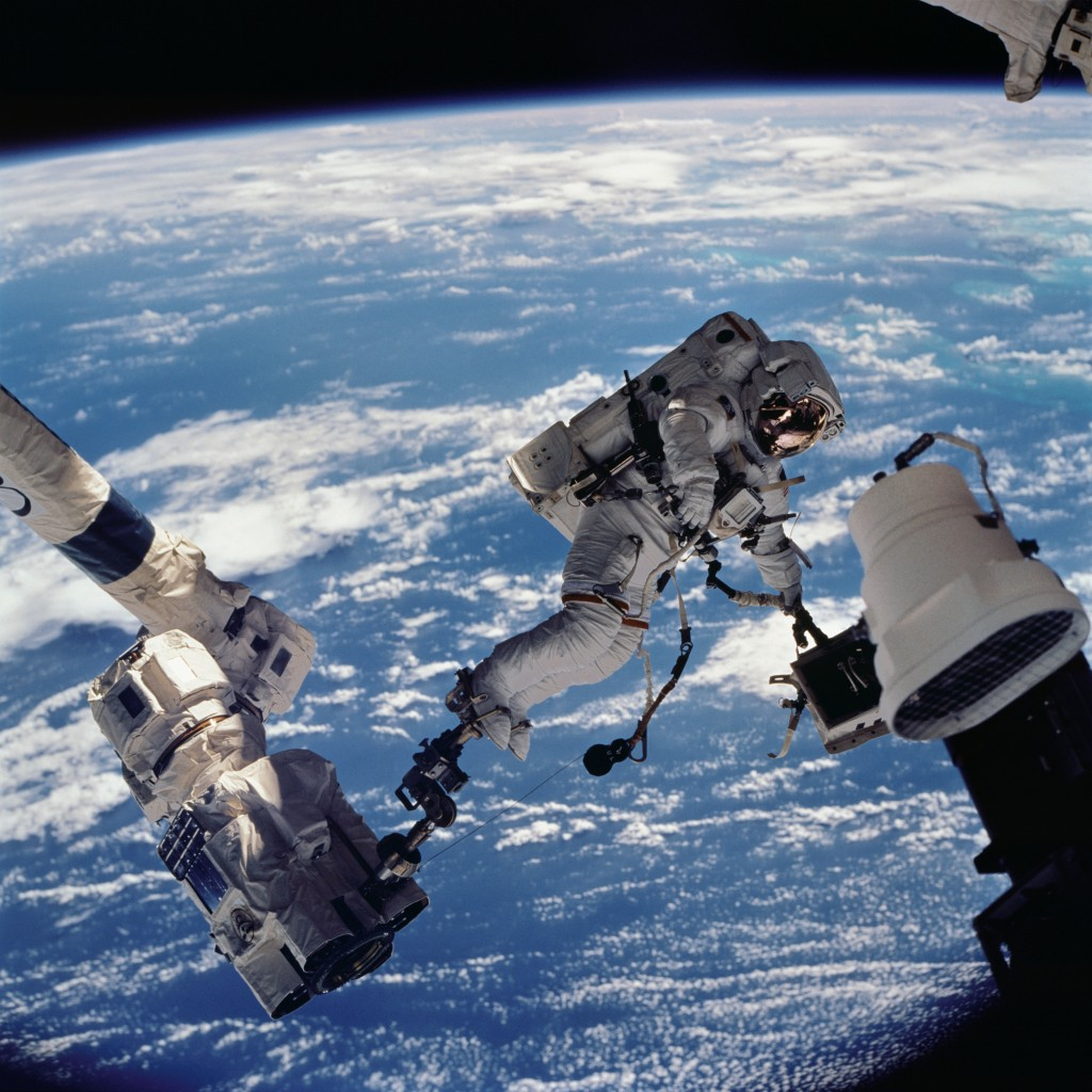 Astronaut David A. Wolf, STS-112 mission specialist, anchored to a foot restraint on the Space Station Remote Manipulator System (SSRMS) or Canadarm2, carries the Starboard One (S1) outboard nadir external camera.
