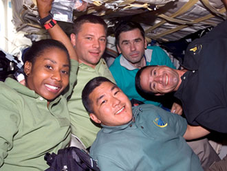 Expedition 16 Flight Engineer Daniel Tani (bottom), Mission Specialists Stephanie Wilson and Doug Wheelock (second left), Expedition 16 Flight Engineer Yuri Malenchenko and Pilot George Zamka take a moment for a photo on the middeck of Space Shuttle Discovery while docked with the International Space Station. Image credit: NASA