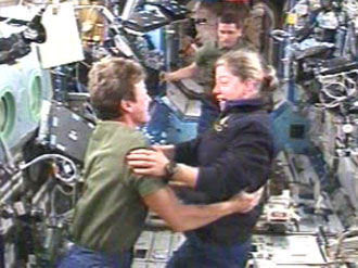Expedition 16 Commander Peggy Whitson (left) welcomes STS-120 Commander Pam Melroy aboard the International Space Station. Image credit: NASA TV
