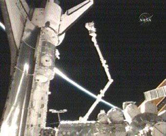 STS-120 Mission Specialist Doug Wheelock rides the station's robotic arm into Discovery's payload bay. Image credit: NASA TV