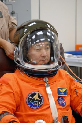 Mission Specialist Daniel Tani has his helmet adjusted during fitting of his launch and entry suit